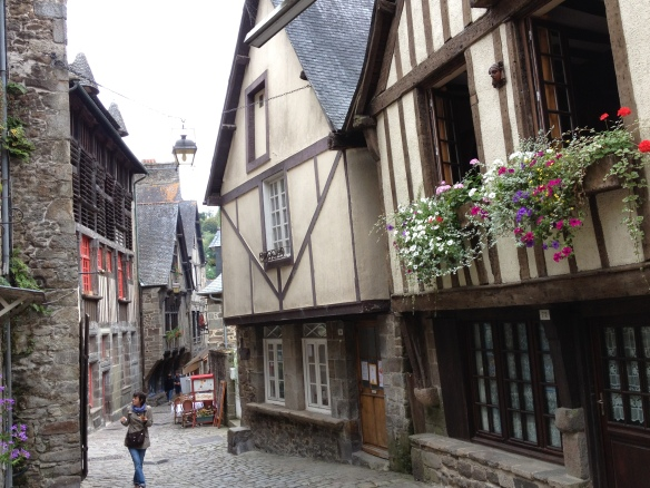 "A scene from rue de Jerzual in Dinan. As May said in a letter home dated April 29, 1870: ""Yesterday we down the oldest street in town, (where, in spite of the steepness, Queen Ann's carriage is said to have trundled over it), to the river which runs at the foot. The houses overhang the street in funny little gabled stories almost shutting out all light from above, and it being very narrow & extremely steep, you can see it was a sensation to have explored it."""
