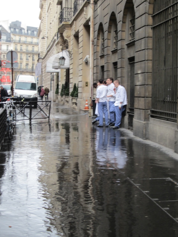 Rainy day, rue Cambon. Students on a cigarrette break from the Ecole Ritz Escoffier, across the street from Chanel Paris.
