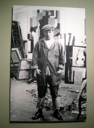 A photograph of Picasso in his rue Schoelcher studio 1915-16. I can almost see what Eva saw in him. . . .
