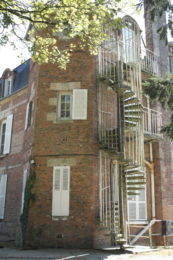 An exterior spiral stairway around the back of one of the chateau's two turrets.